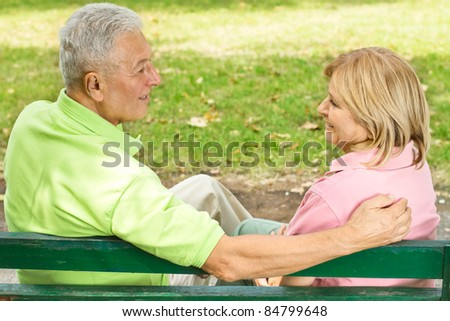 Elderly couple sitting and talking on park bench. - stock photo