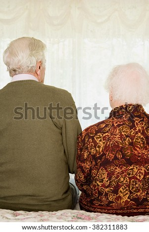 Elderly couple sitting on bed - stock photo