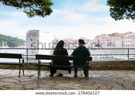 elderly couple sitting on bench watching Dubrovnik panorama - stock photo