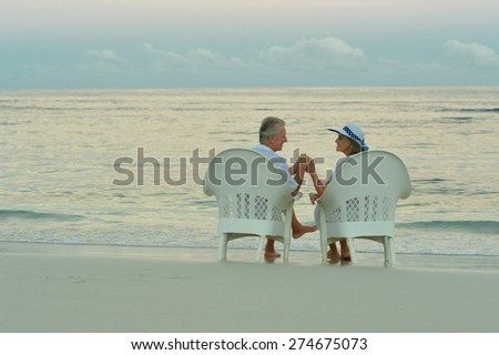 Elderly couple sitting on the shore and looking at each other - stock photo