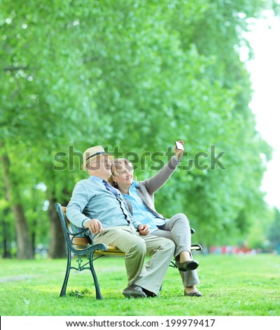 Elderly couple taking a selfie in the park seated on a wooden bench shot with tilt and shift lens - stock photo