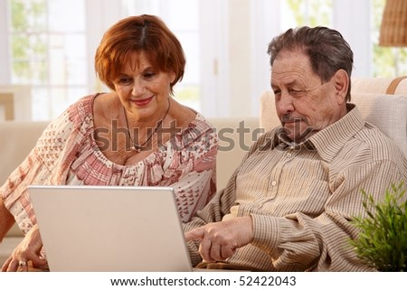 Elderly couple using laptop computer at home, looking at screen, smiling. - stock photo