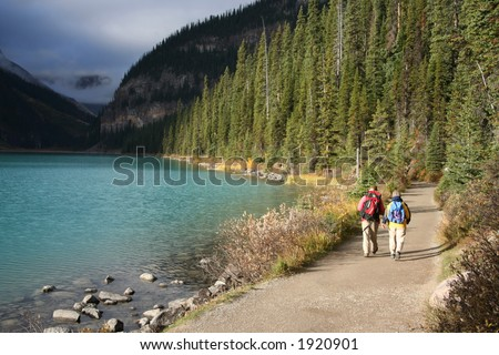 elderly couple walking beside Lake Louise Canadian Rockies - stock photo