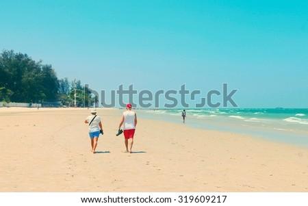 Elderly couple walking on the beach - Instagram filter - stock photo