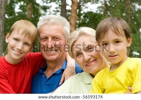 elderly couple with their grandchildren in a summer park - stock photo