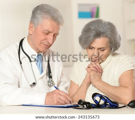 Elderly doctor with a patient - stock photo