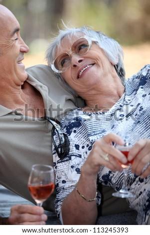 Elderly drinking wine. - stock photo