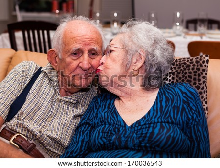 Elderly eighty plus year old couple in an affectionate pose in a home setting. - stock photo