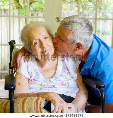 Elderly eighty plus year old woman in a wheel chair in a home setting with her son. - stock photo