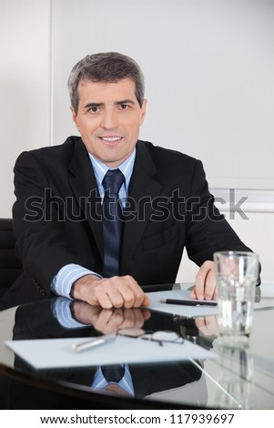 Elderly entrepreneur sitting at his desk in his office - stock photo