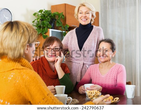 Elderly female having cup of hot tea indoor and smiling - stock photo