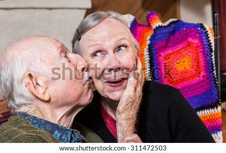 Elderly gentleman kissing woman on cheek in indoors - stock photo