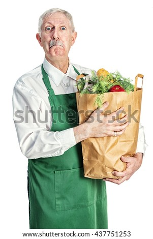 Elderly grocer holding a paper bag full of groceries with a snooty look on his face. - stock photo