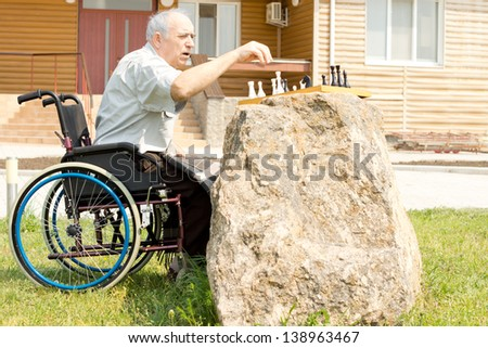 Elderly handicapped man playing chess sitting in his wheelchair in front of his house in the garden with the chessboard on top of a convenient rock - stock photo