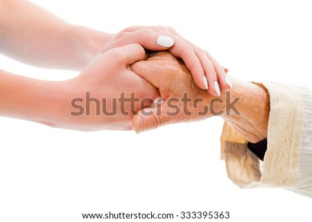 Elderly hands held by a young person - helping concept. - stock photo