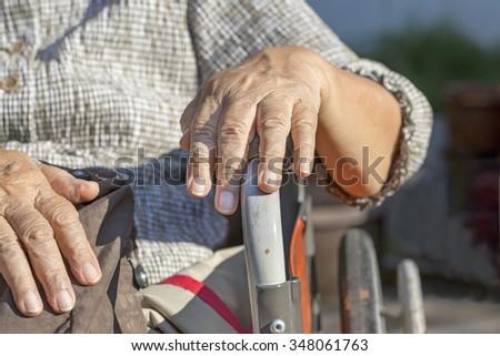 Elderly hands on a wheelchair. - stock photo