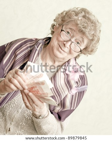 elderly happy woman with pack of money - stock photo