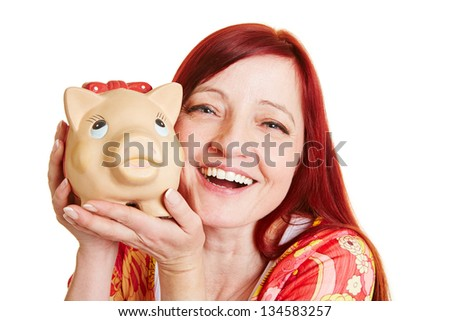 Elderly happy woman with piggy bank near her face - stock photo