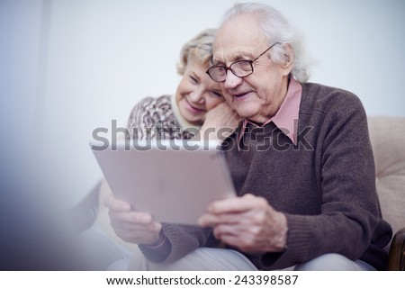 Elderly husband and wife using touchpad - stock photo
