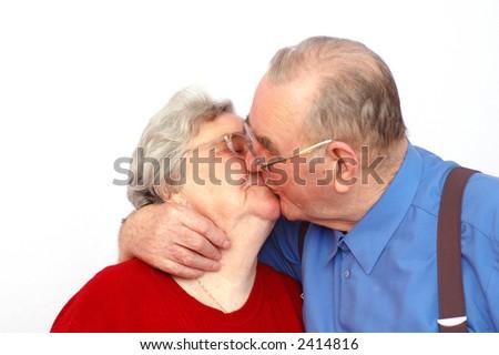 Elderly kissing couple, isolated on white background - stock photo