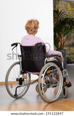 Elderly lady during sitting on wheelchair, vertical - stock photo