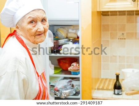 Elderly lady in the kitchen at home preparing to cook. - stock photo