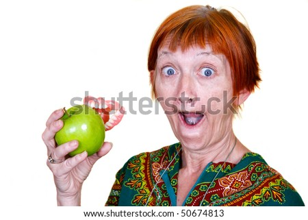 Elderly lady losing her teeth on a bite of an apple - stock photo