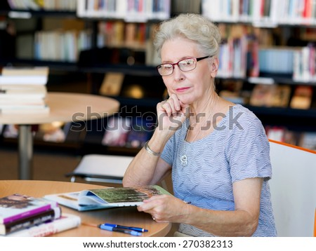 Elderly lady reading books in library - stock photo