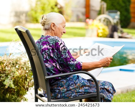 Elderly lady reading newspaper peacefully in her beautiful garden. - stock photo