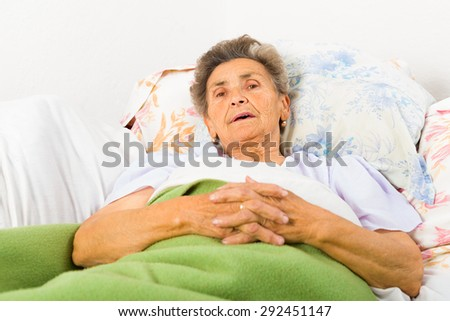 Elderly lady saying her daily prayers in bed before sleep. - stock photo