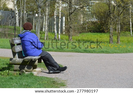 Elderly lady sitting alone on a wooden bench outdoors. Old woman getting fresh air and resting on a bench. Concept of pensioner or widow loneliness and sadness. Mature female in autumn outfit. - stock photo