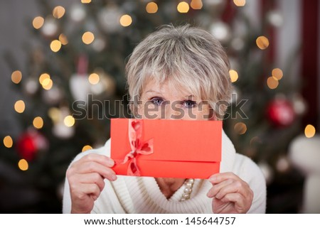 Elderly lady with a red gift Christmas voucher held up in front of her face as she stands in front of a tree with a sparkling bokeh of lights - stock photo
