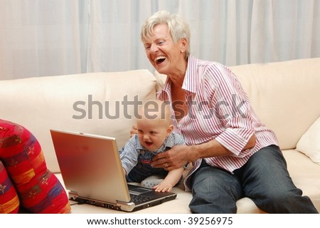 Elderly Lady with Baby abd Laptop - stock photo