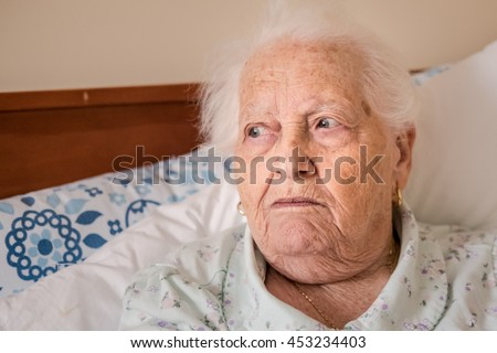 Elderly lady with eyes looking into left third.Sitting up in bed with cushions behind. Hair messy. - stock photo