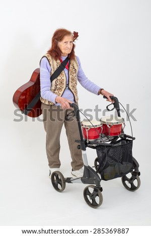 Elderly lady with rollator and musical instruments. - stock photo