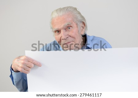 Elderly looking at camera while showing a blank whiteboard for advertising or the message of an awareness campaign - stock photo