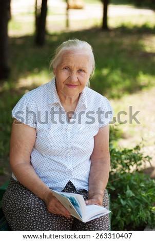 Elderly lovely senior woman sitting in a park, reading book - stock photo