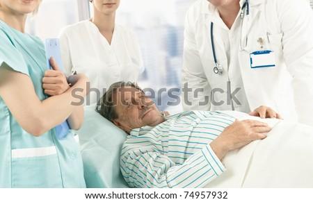 Elderly male patient lying in hospital bed wearing pyjama, medical team around.? - stock photo