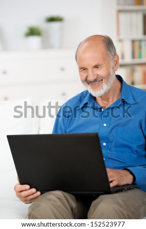 Elderly male pensioner working on a laptop at home smiling as he reads the screen and balances it on his knee while sitting on a sofa - stock photo