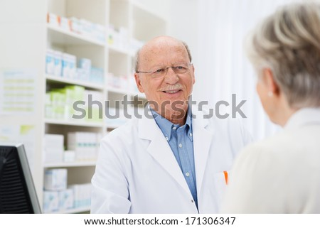 Elderly male pharmacist talking to a senior patient with a view over the womans shoulder to his face - stock photo