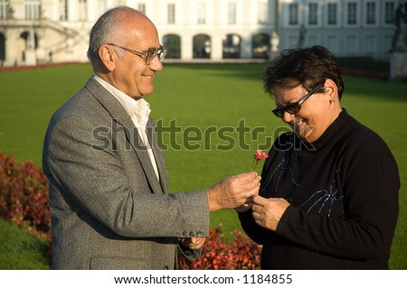 elderly man and woman hugging in park - stock photo
