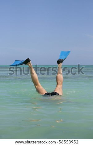 Elderly man bathing in the sea with diving fins on feet - stock photo