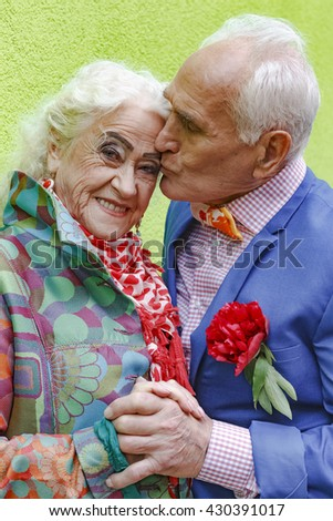 Elderly man confesses his love and kisses an elderly woman on a background of green wall. Bright make up and fashionable beautiful clothes. Concept of love, passion, date. - stock photo