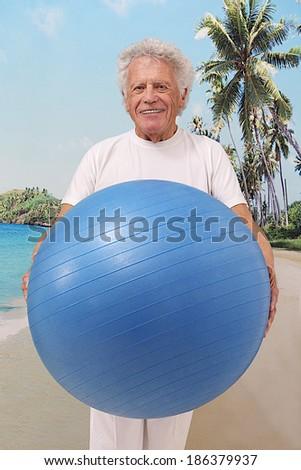 Elderly man doing yoga exercises with a gym  ball  - stock photo