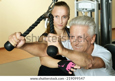 Elderly man exercising in gym with trainer - stock photo