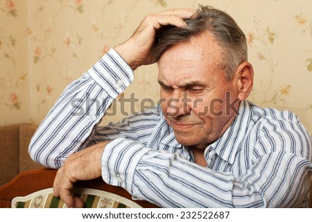 Elderly man grieves at home. Single people. Man upset headache - stock photo