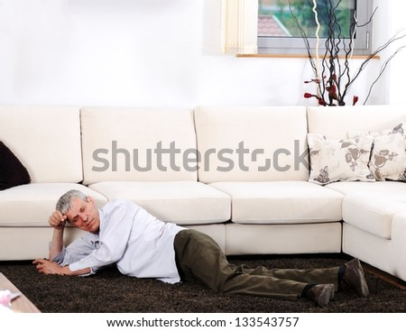 Elderly man having heart attack lying on floor at home - stock photo