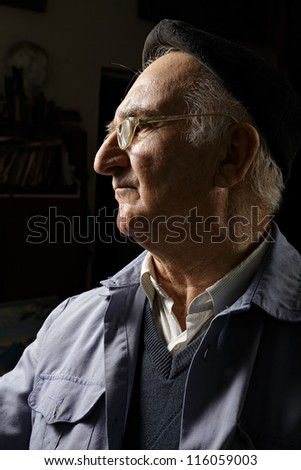 Elderly man in cap and eyeglasses sideview in darkness - stock photo