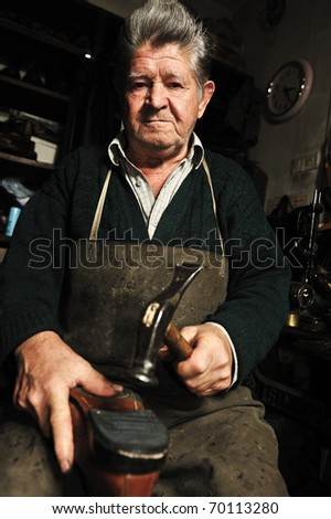 Elderly man in his workshop repairing a shoe with a hammer - stock photo