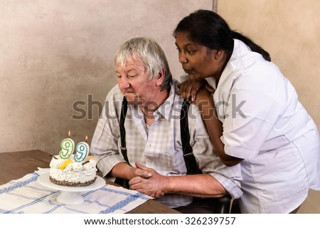 Elderly man in nursing home blowing out candles on his birthday cake - stock photo